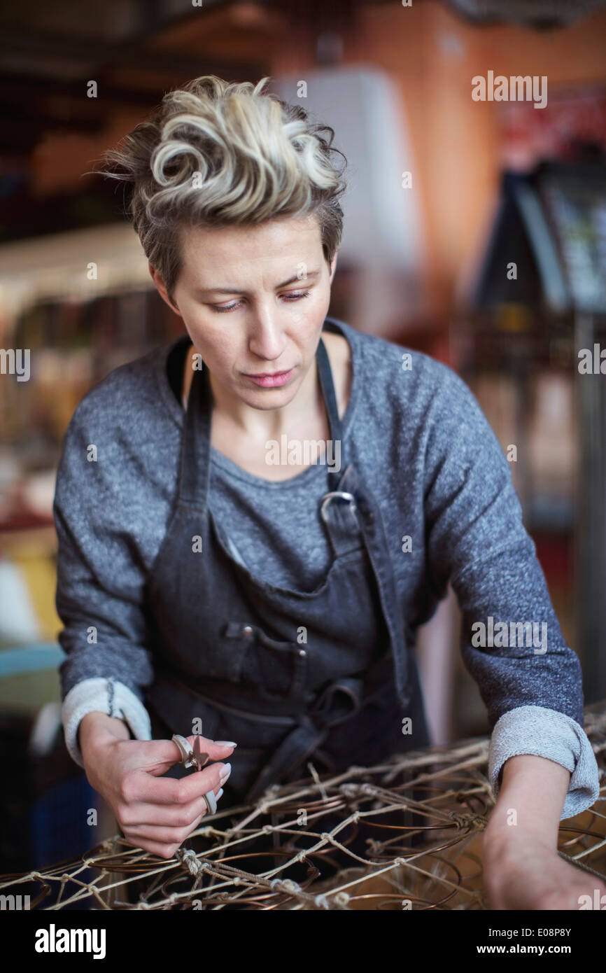 Female worker making chaise longue at workshop - Stock Image