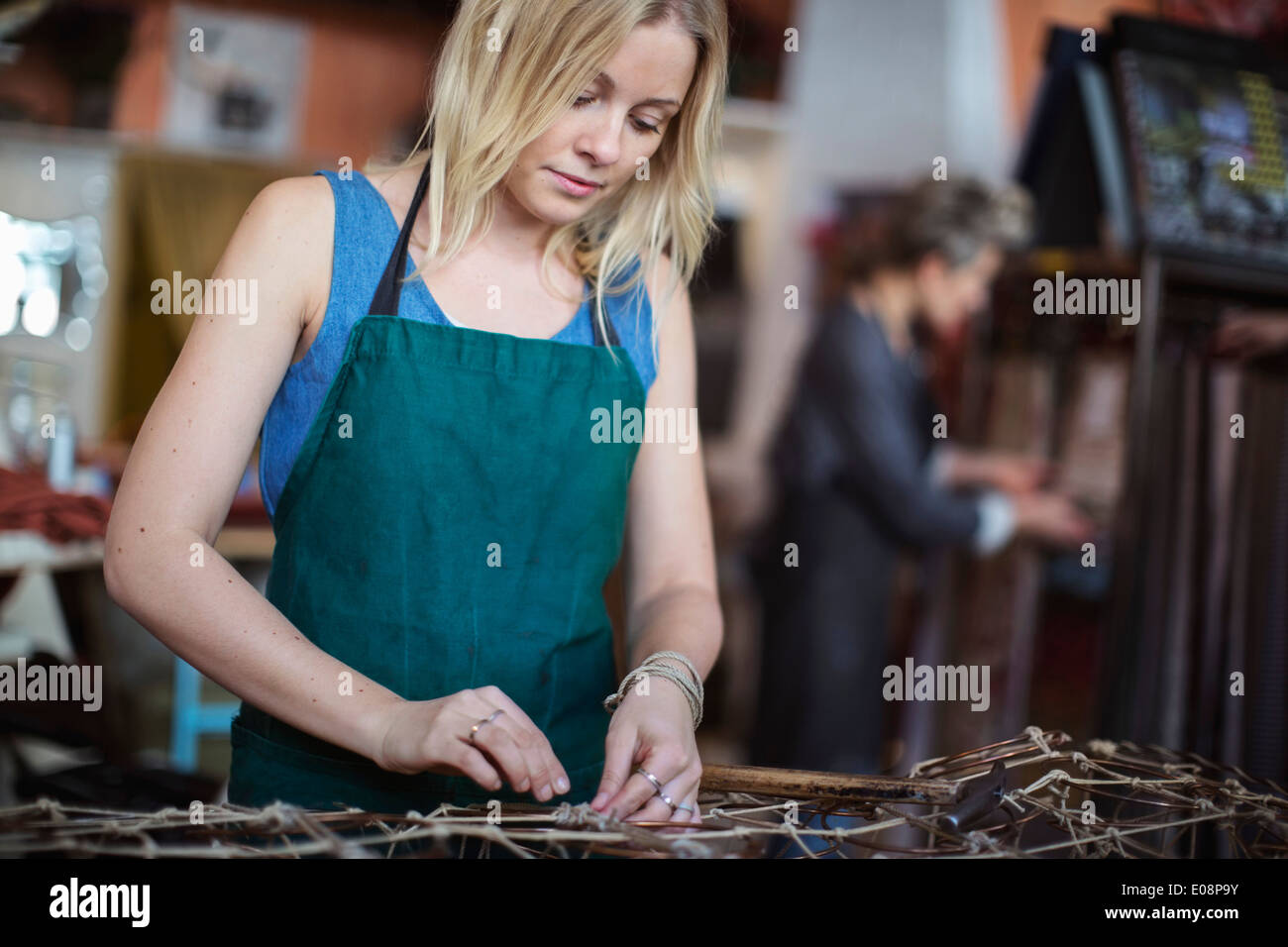 Young female worker making chaise longue at workshop - Stock Image
