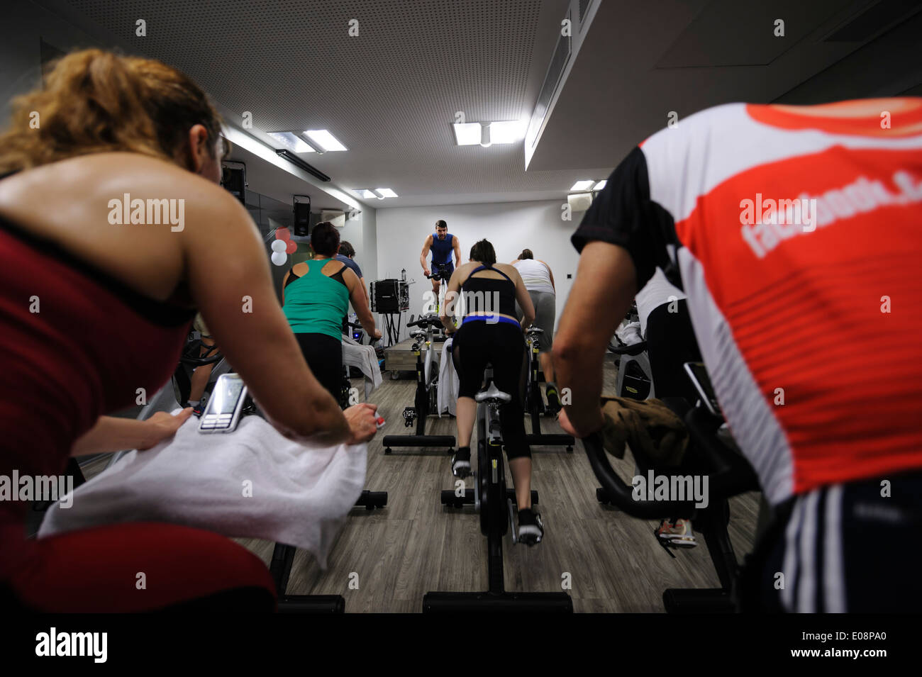View from the back of people riding stationary bicycle during a spinning class at the gym - Stock Image