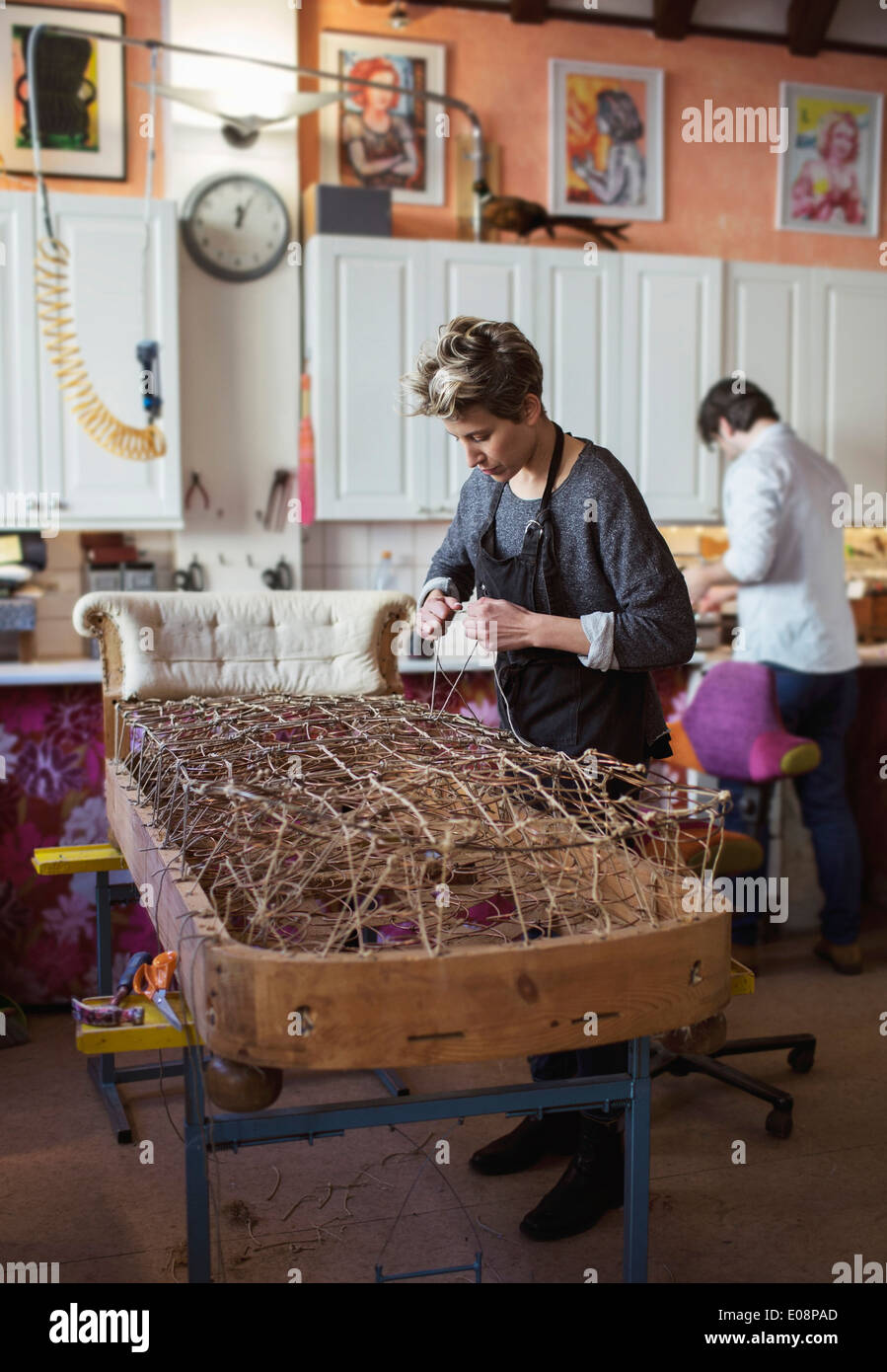Female worker fixing rope on chaise longue at workshop - Stock Image