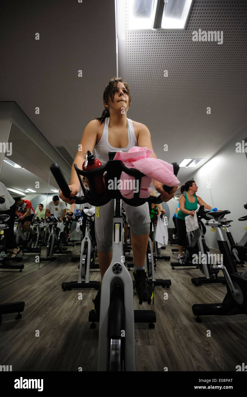 Young woman riding stationary bicycle during a spinning class at the gym - Stock Image