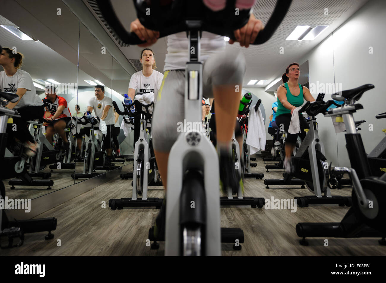 People riding stationary bicycles during a spinning class at the gym - Stock Image