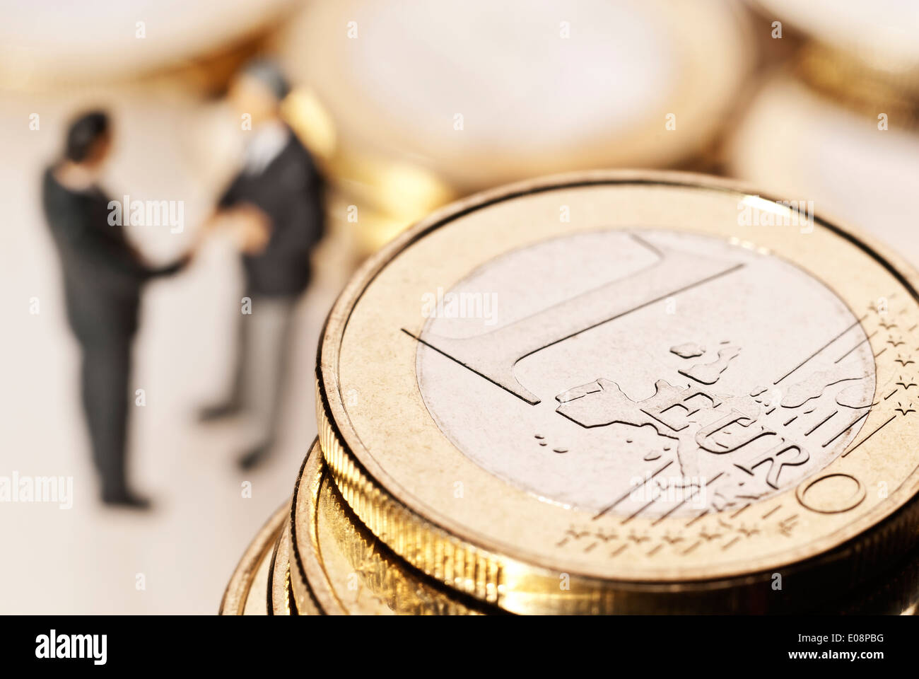 Euro coins and two businessmen in the background Stock Photo