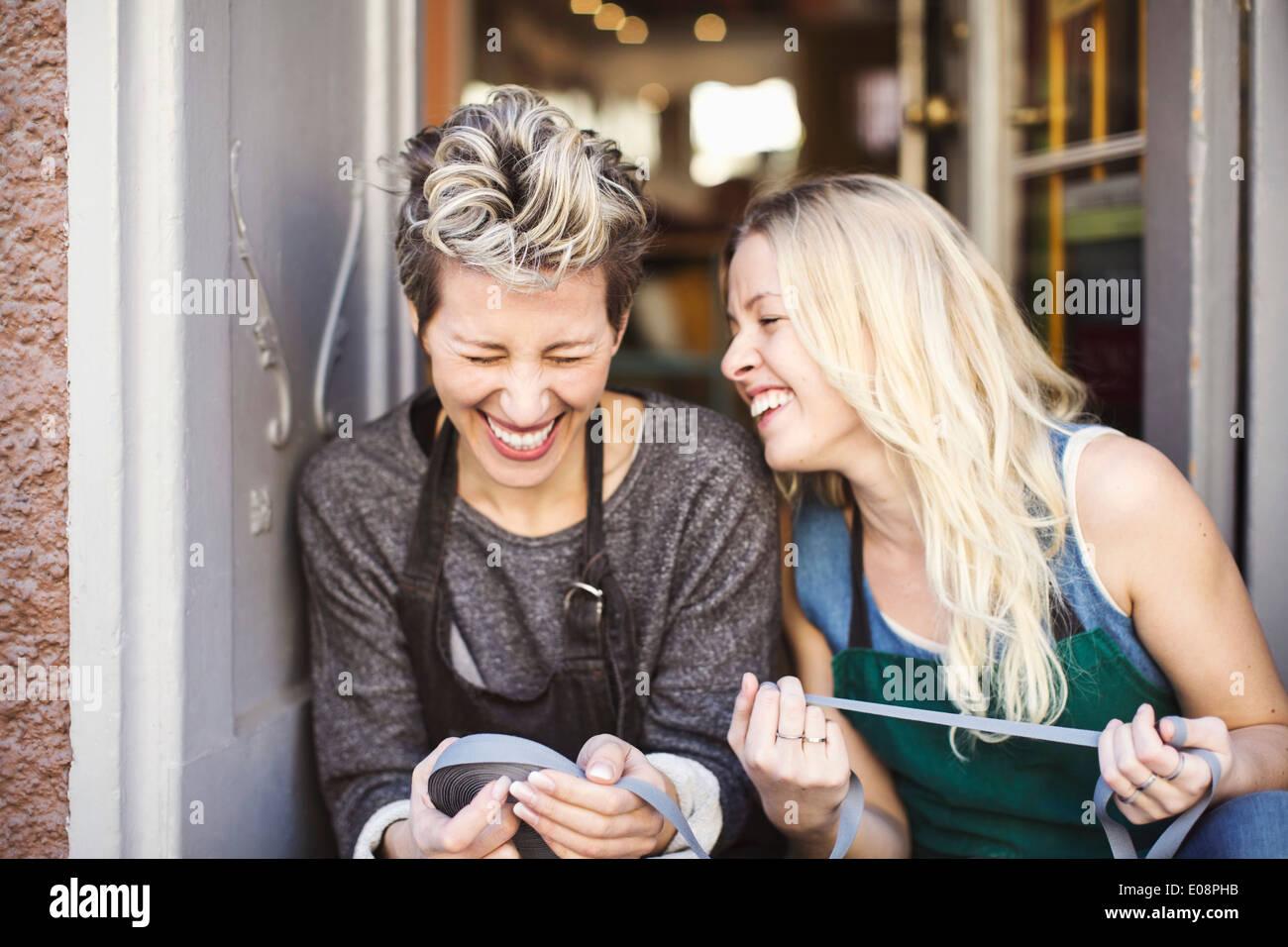 Happy fashion designers with ribbon spool sitting at studio doorway - Stock Image