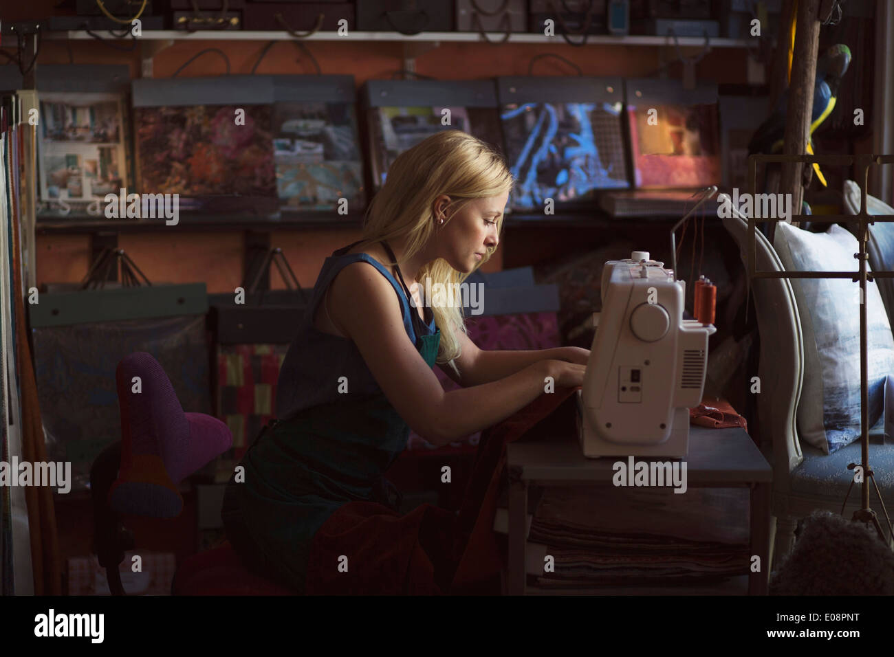 Side view of young fashion designer using sewing machine in studio - Stock Image