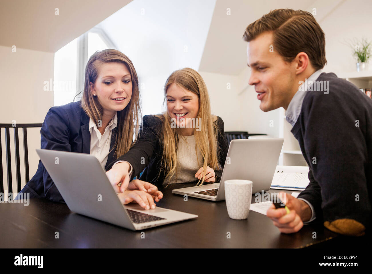 Business People Working Together On Laptop At Desk In Office Stock