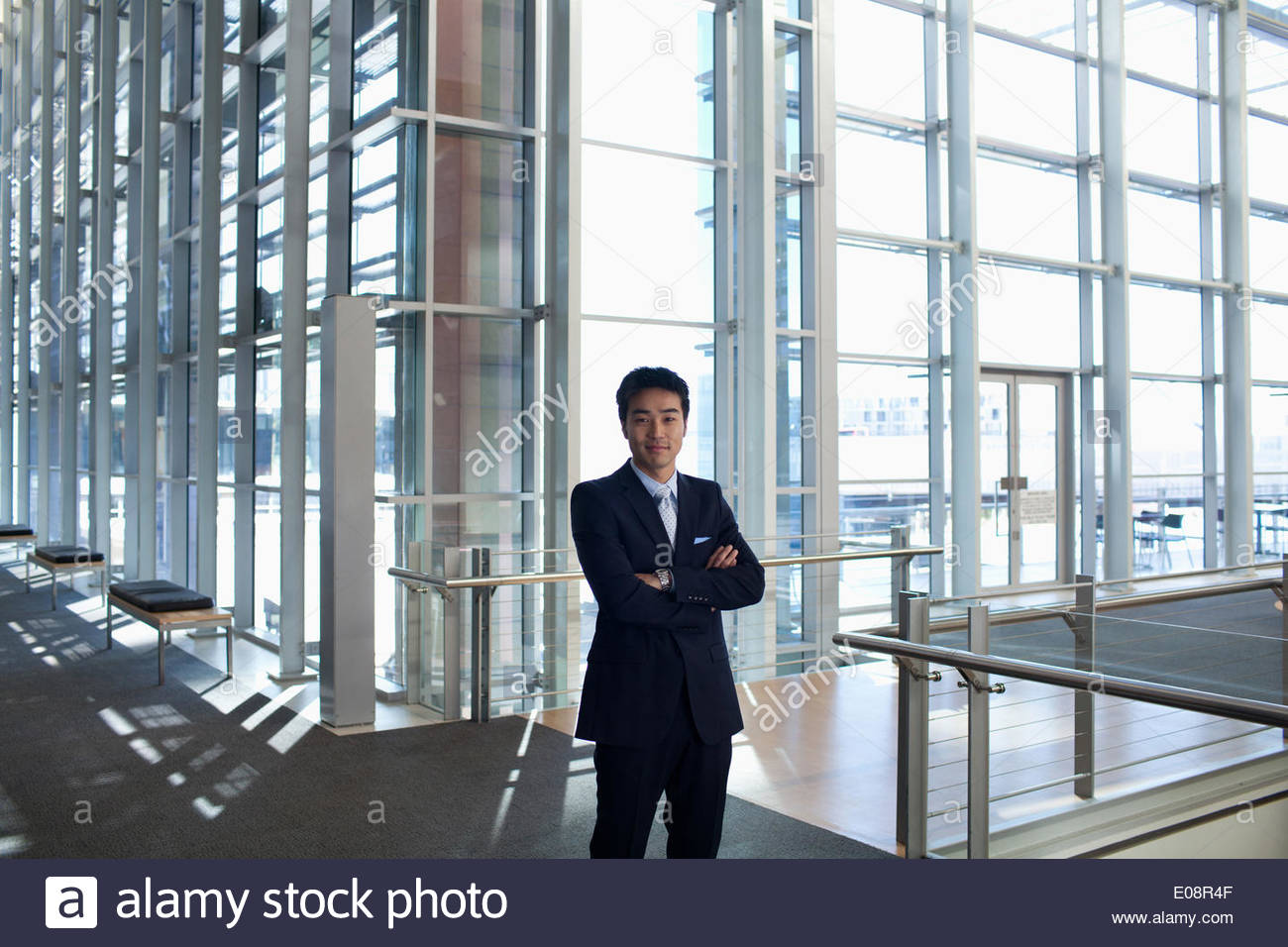 Portrait of smiling businessman in modern lobby - Stock Image