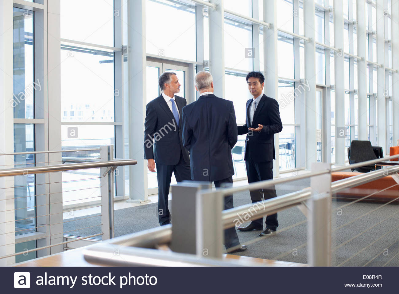 Business people meeting at window in office lobby - Stock Image