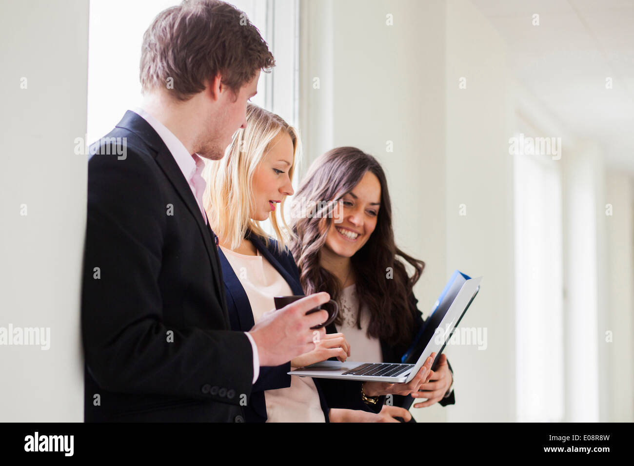 Business colleagues using laptop while standing in office - Stock Image