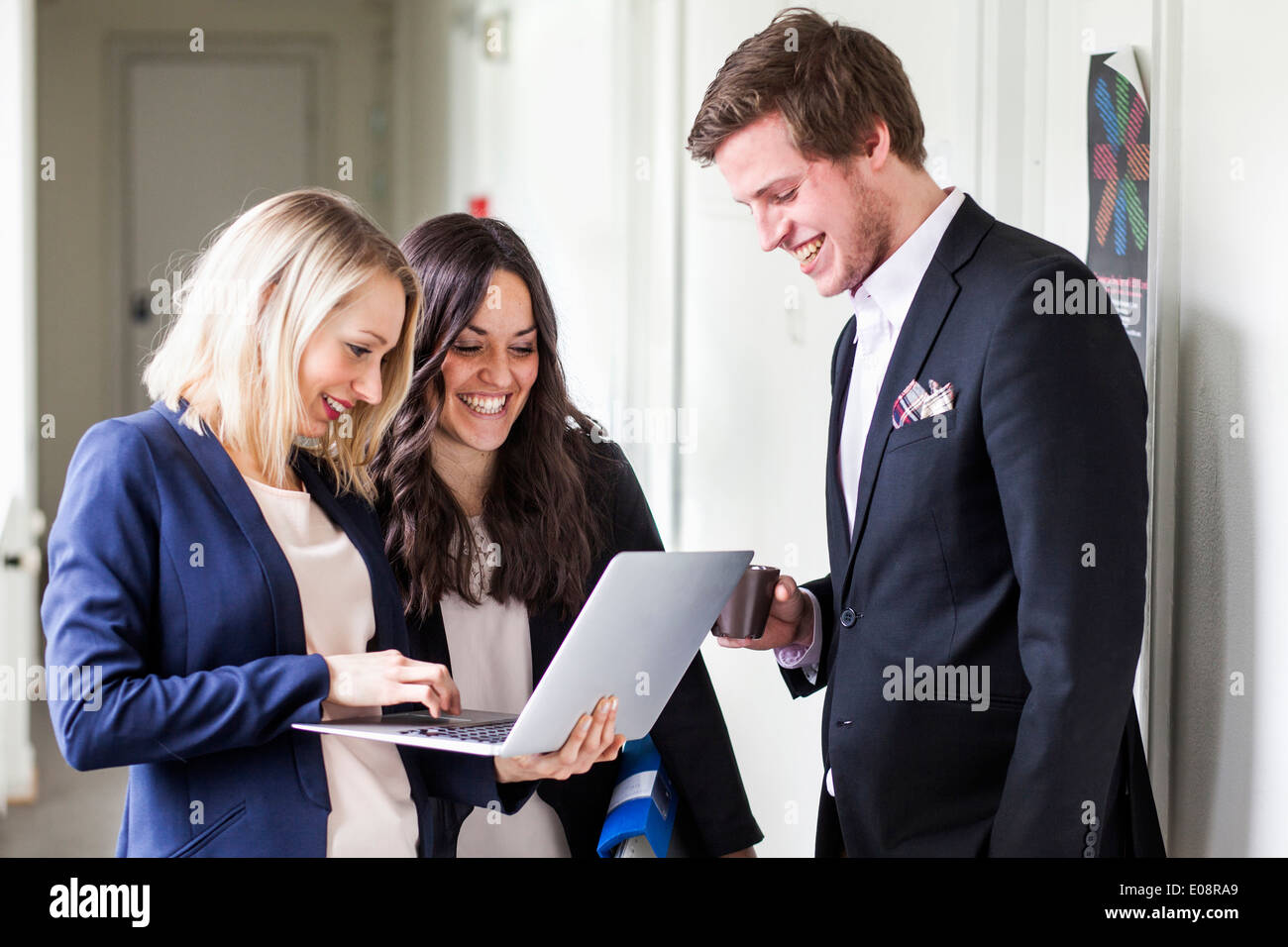 Business people using laptop in office corridor - Stock Image