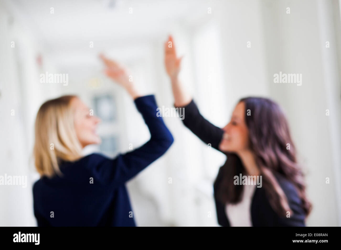 Defocused image of successful businesswomen giving high-five in office - Stock Image