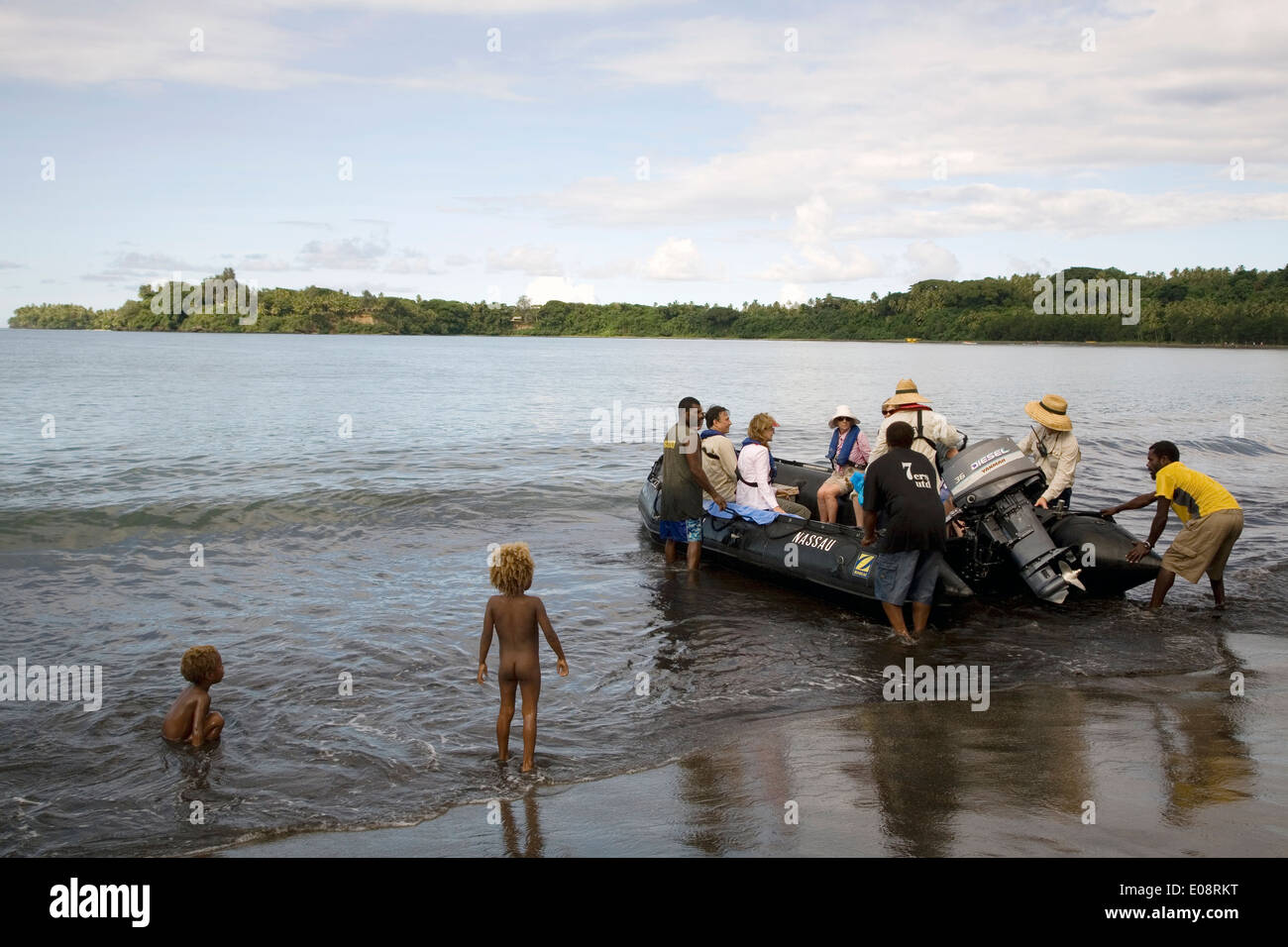 Orion guests arrive ashore at Tanna Island via Zodiac to the greeting of Chief Philemon (green sulu), Vanuatu, South Pacific - Stock Image