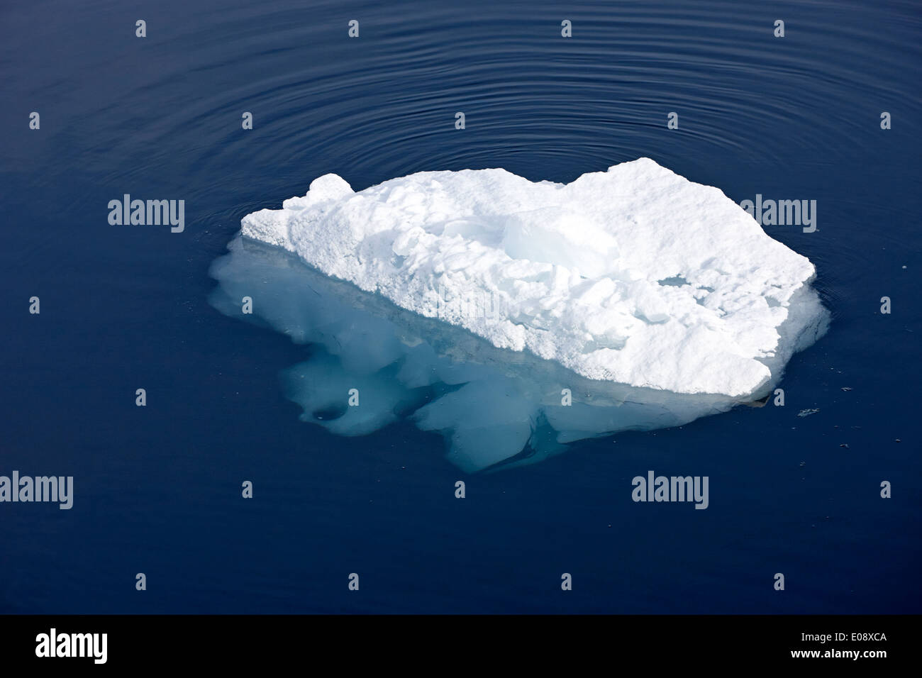 small iceberg with small portion above waterline and huge volume below Antarctica - Stock Image