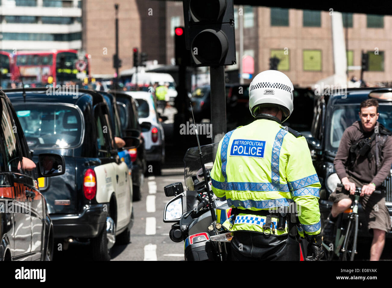 London, UK. 6th May 2014, A Metropolitan Motorcycle officer watches helplessly as taxis jam the streets of Southwark in protest over the refusal to place a Black Cab taxi rank outside the entrance to The Shard. Photographer:  Gordon Scammell/Alamy Live News - Stock Image