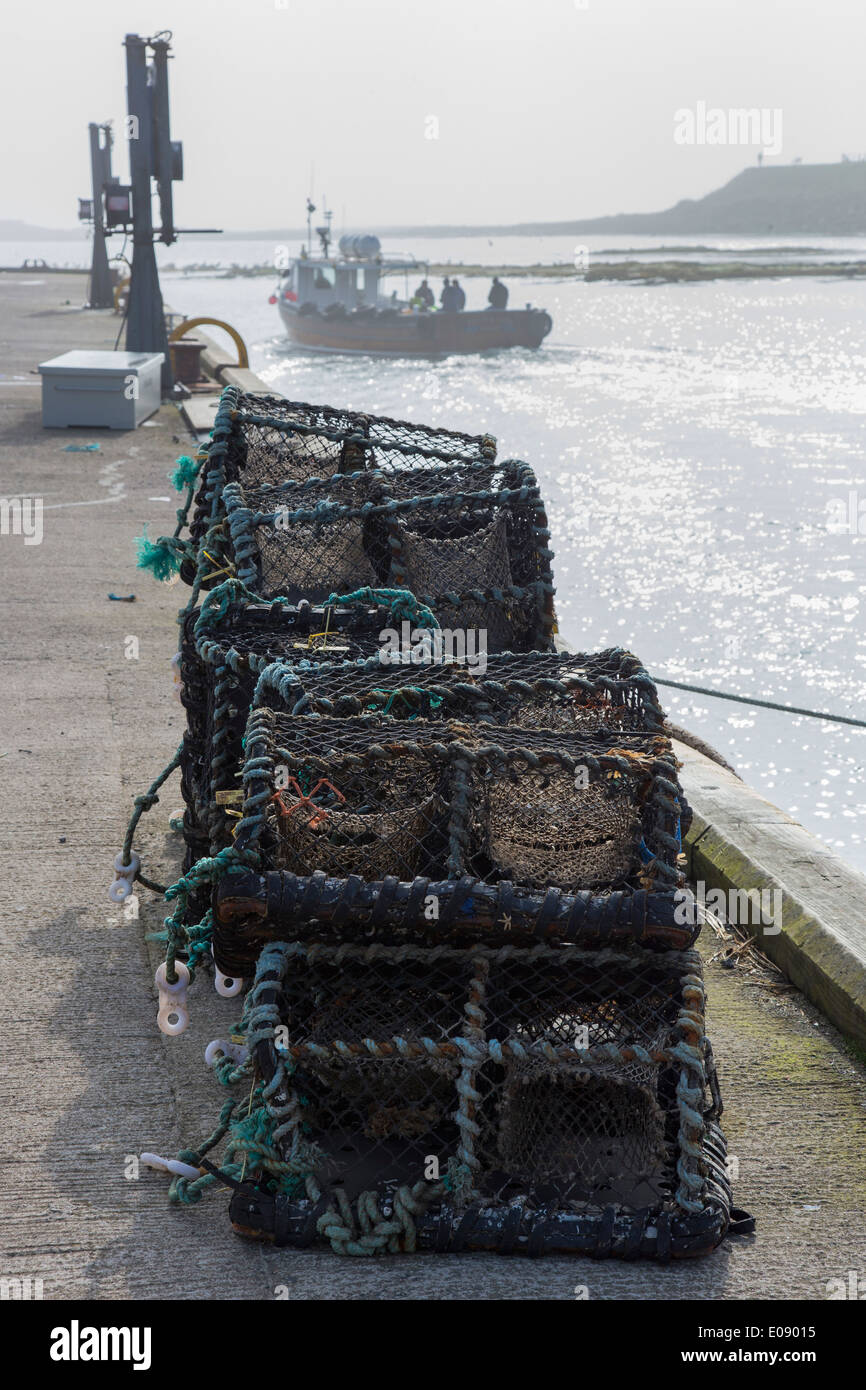 Lobster pots and fishing boat heading out, Seahouses harbour, Northumberland, UK, April 2014 - Stock Image