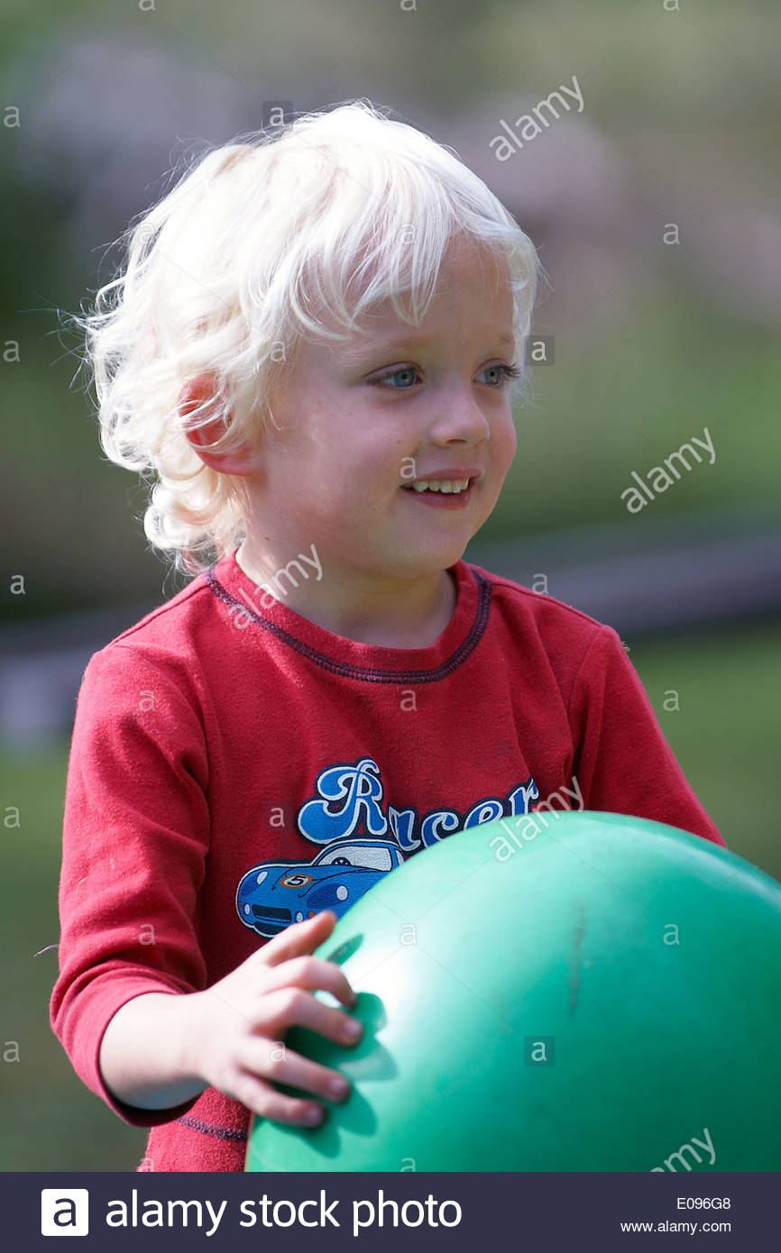 A little blonde-haired boy, holding a large green ball and smiling off-camera; at Cawongla Playhouse pre-school, Cawongla, NSW, Australia. - Stock Image