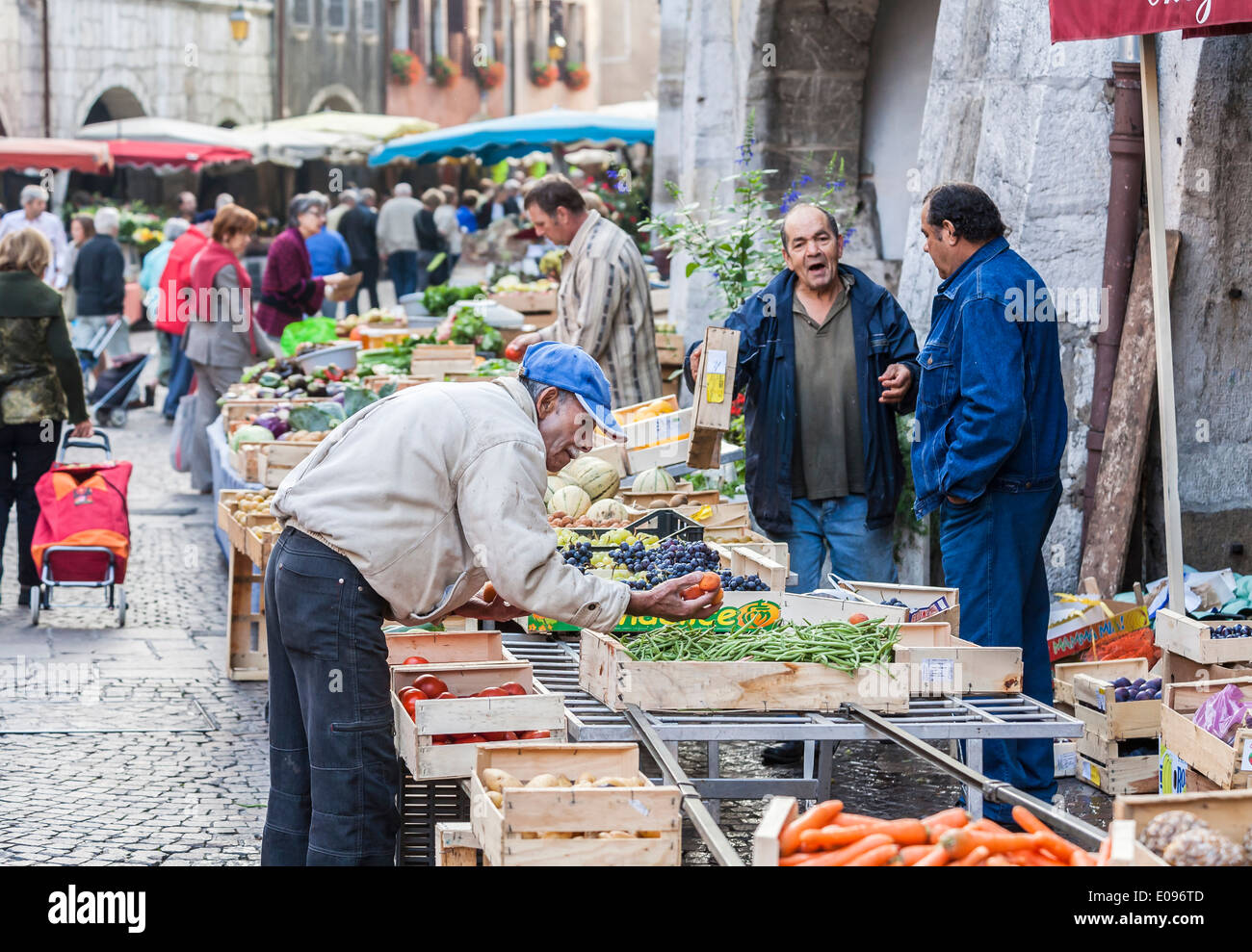 Elderly Frenchman inspects produce at a fruit and vegetable market stall in Annecy, France as stallholders converse - Stock Image