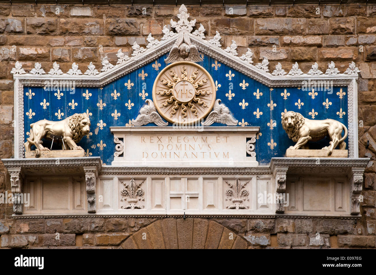 Marble frontispiece of 1528 with two gilded lions on Palazzo Vecchio Florence Italy There is a glory and the monogram of Christ - Stock Image