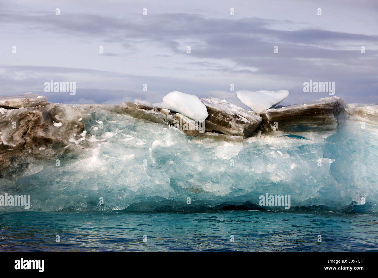 dirty layer at top of inverted iceberg taken from glacial ice cierva cove Antarctica - Stock Image