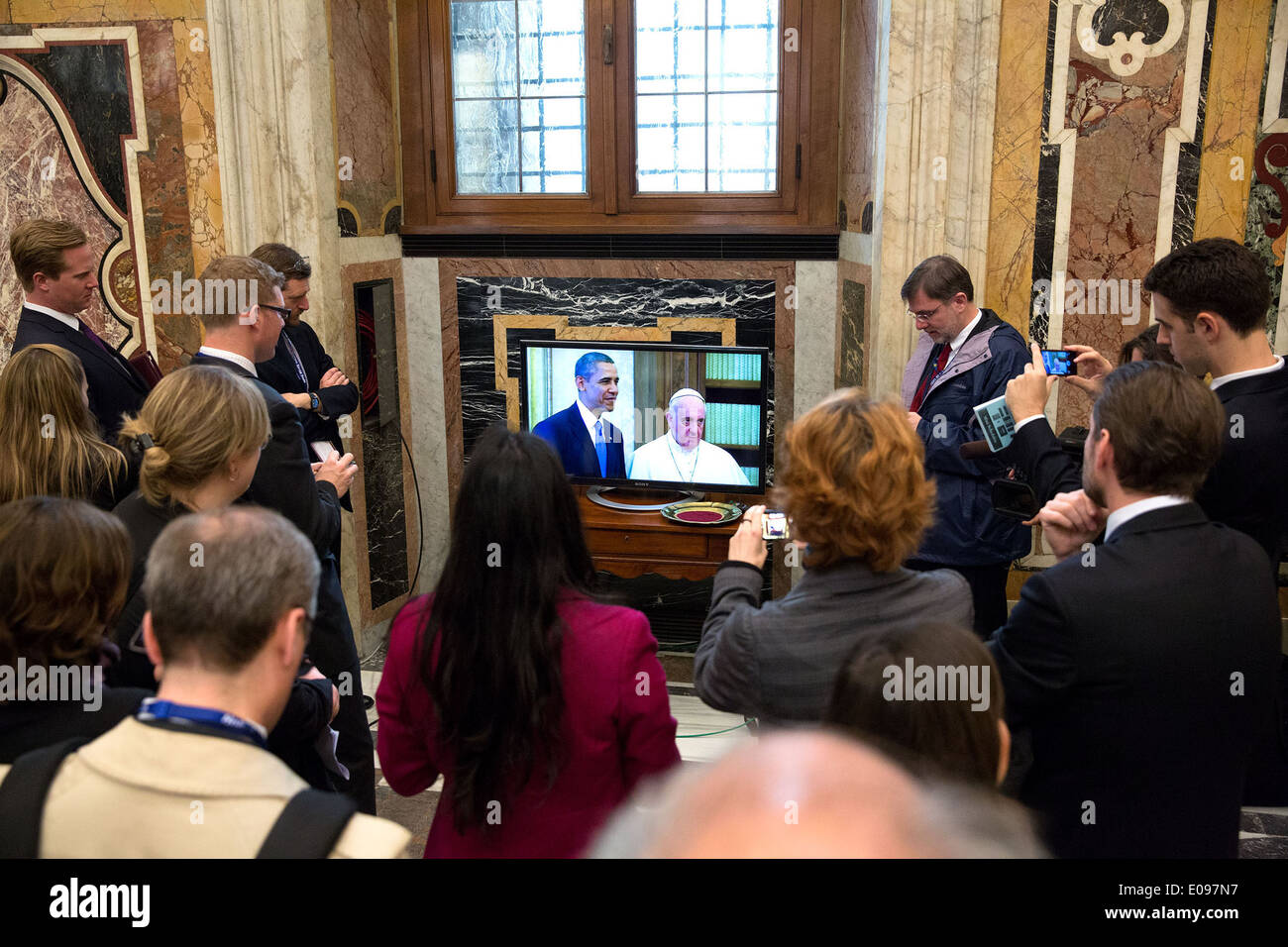 Members of the press watch on closed-circuit television as President Barack Obama meets with Pope Francis at the Vatican, March - Stock Image
