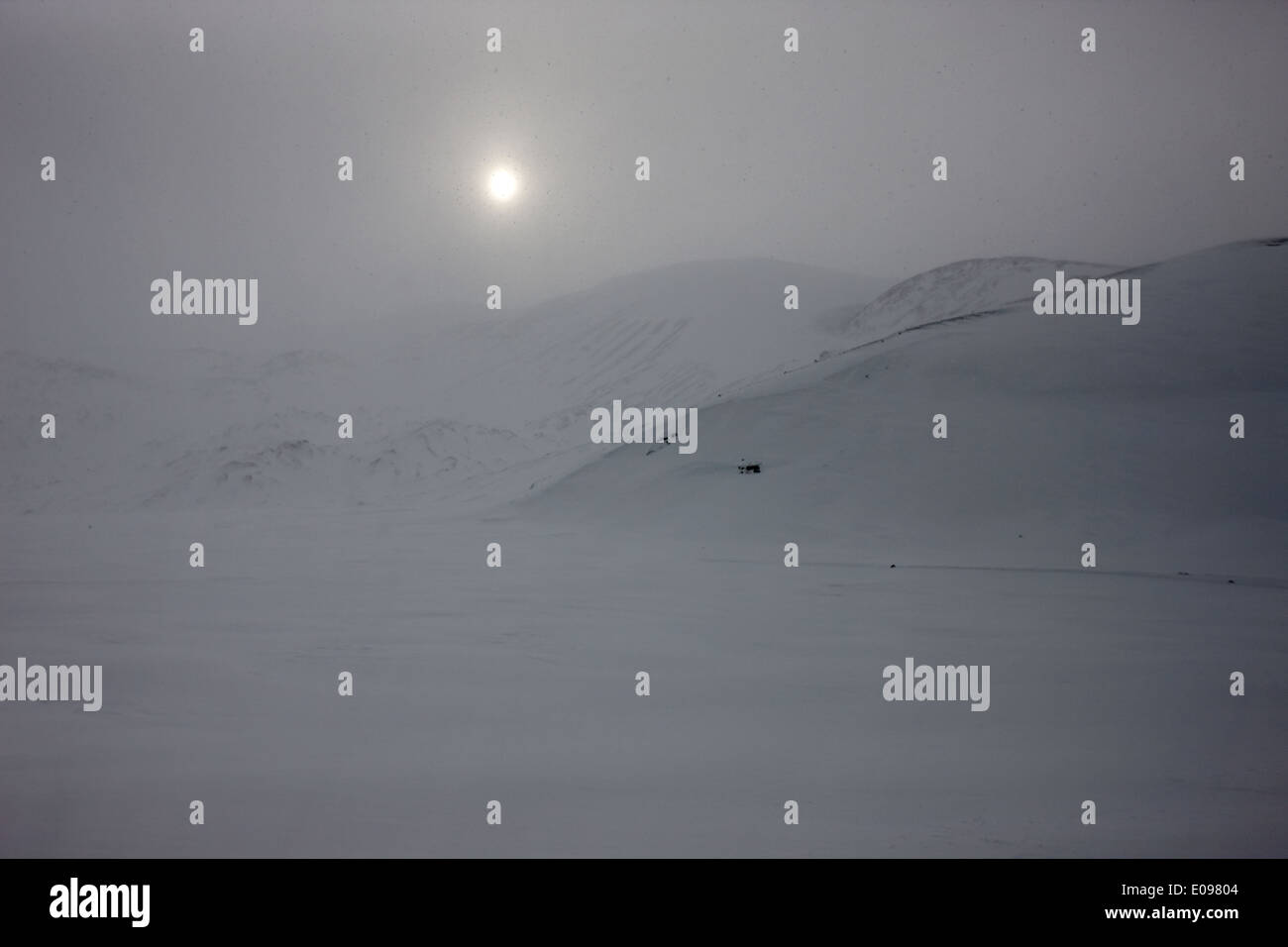 sun breaking through white out snowstorm whalers bay deception island Antarctica - Stock Image