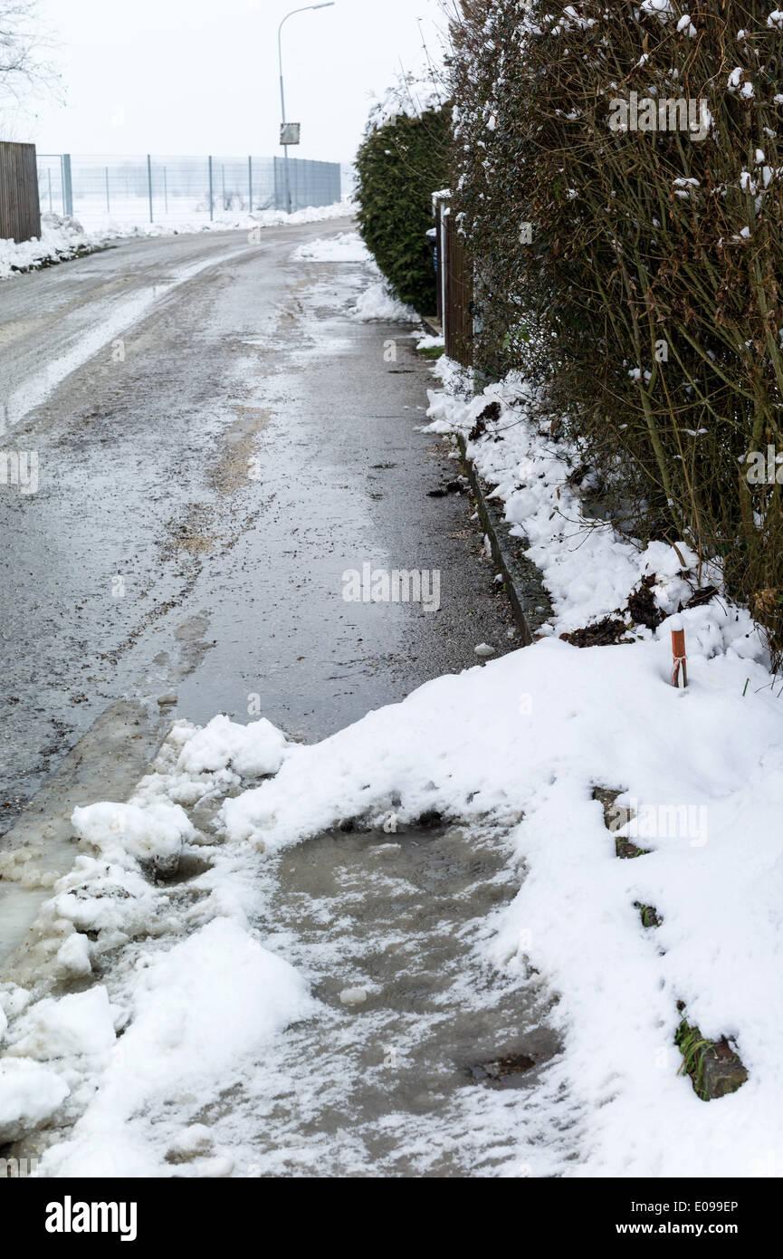 Snow on sidewalk and street, symbolic photo for accident risk and Raeumpflicht, Schnee auf Gehweg und Strasse, Symbolfoto Stock Photo