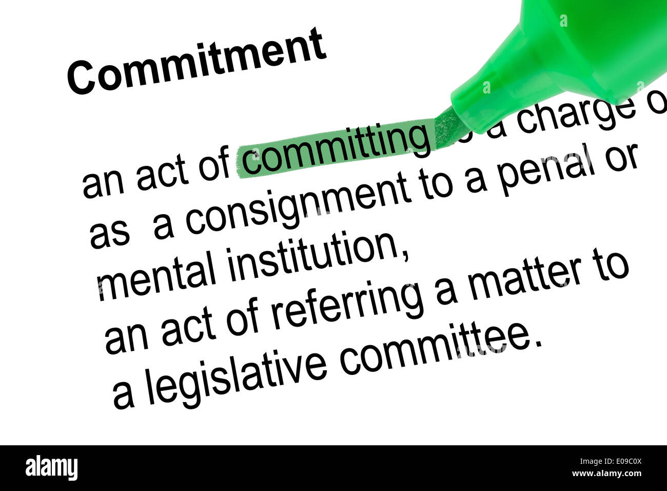 Highlighted word committing for Commitment with green pen over white paper. Isolated white background. - Stock Image