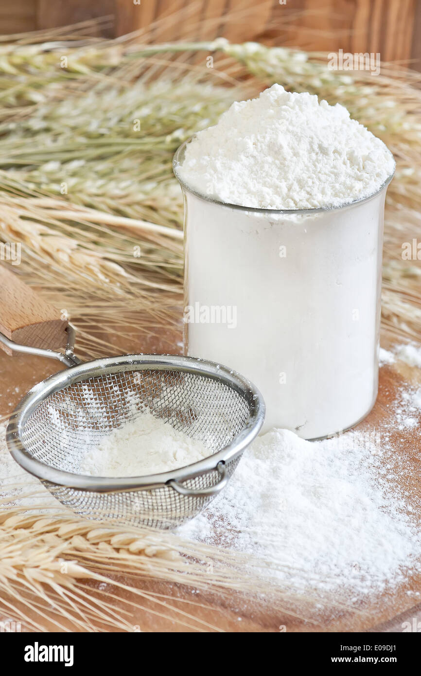 Wheat flour in glass, sifter and grains. Selective focus. - Stock Image