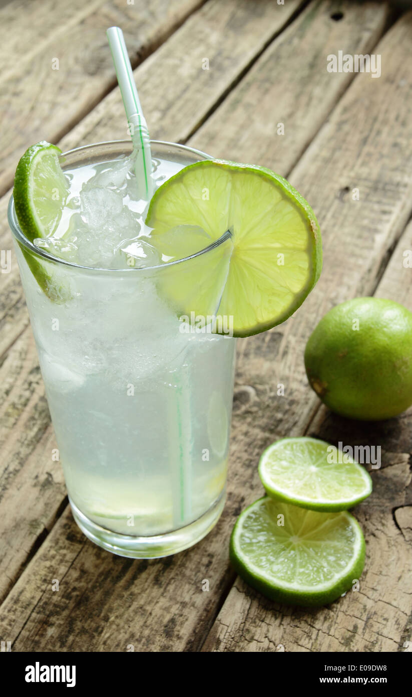 Cold and fresh drink with lime and ice on wooden table - Stock Image
