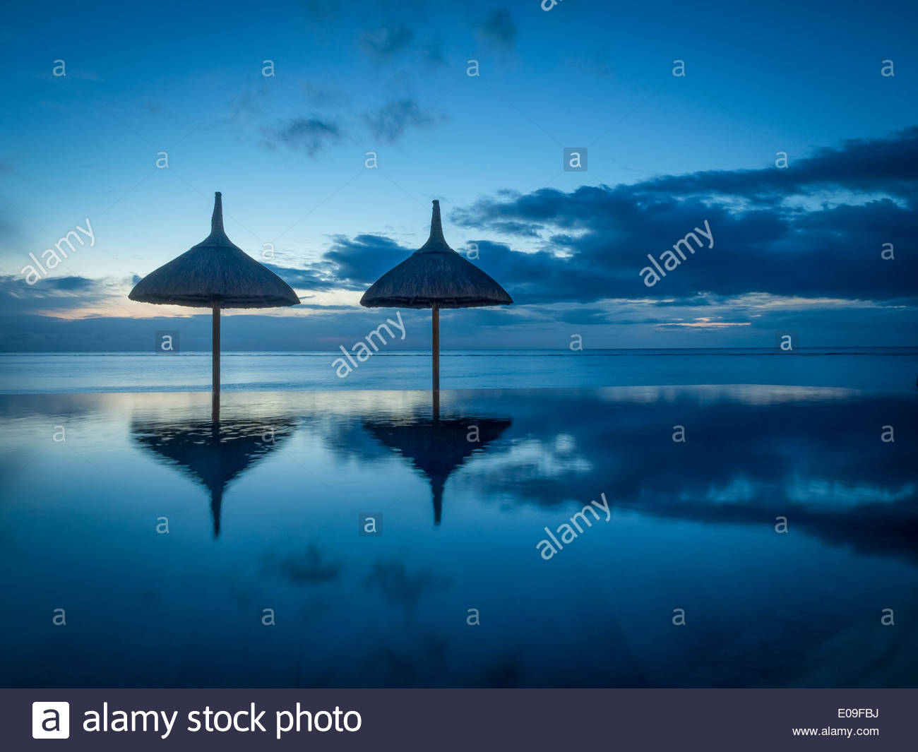 Mauritius, La Preneuse, two sunshades at swimming pool in front of the sea - Stock Image
