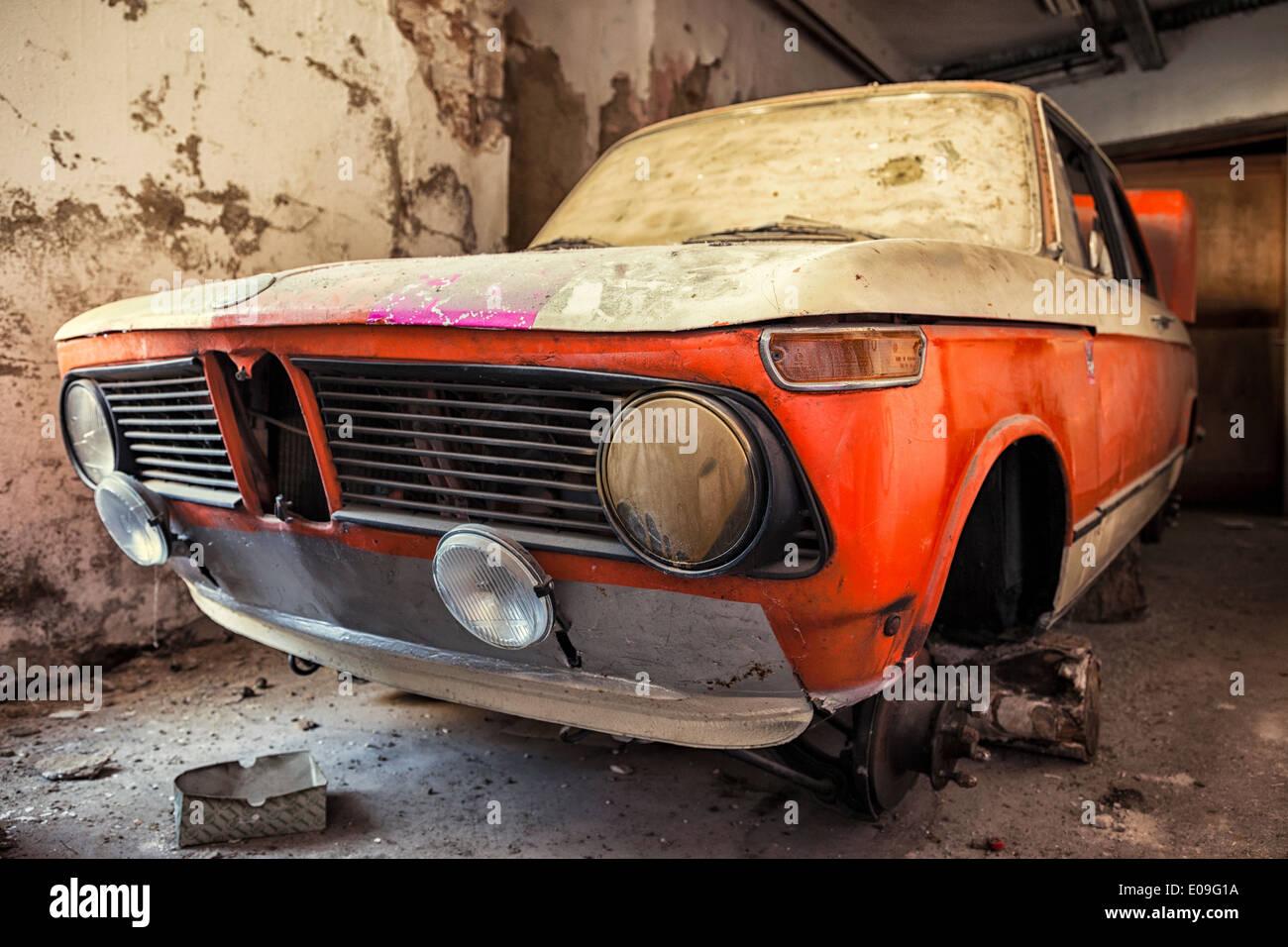 Incomplete vintage car in garage - Stock Image