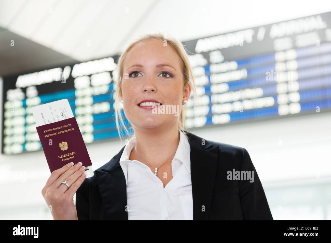 Woman with passport and flight tickets on an airport waits for her takeoff in the vacation., Frau mit Reisepass und Flugtickets - Stock Image