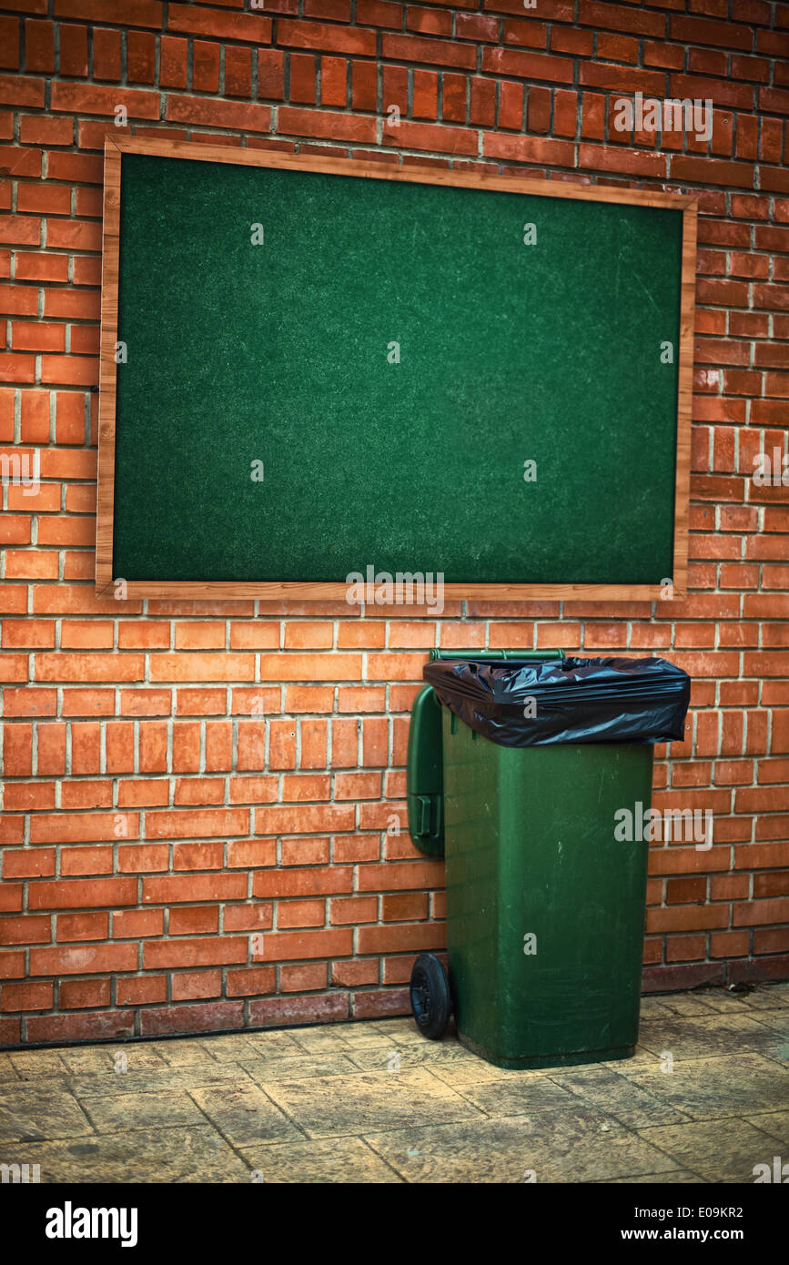 Green garbage can with plastic bag on the street - Stock Image
