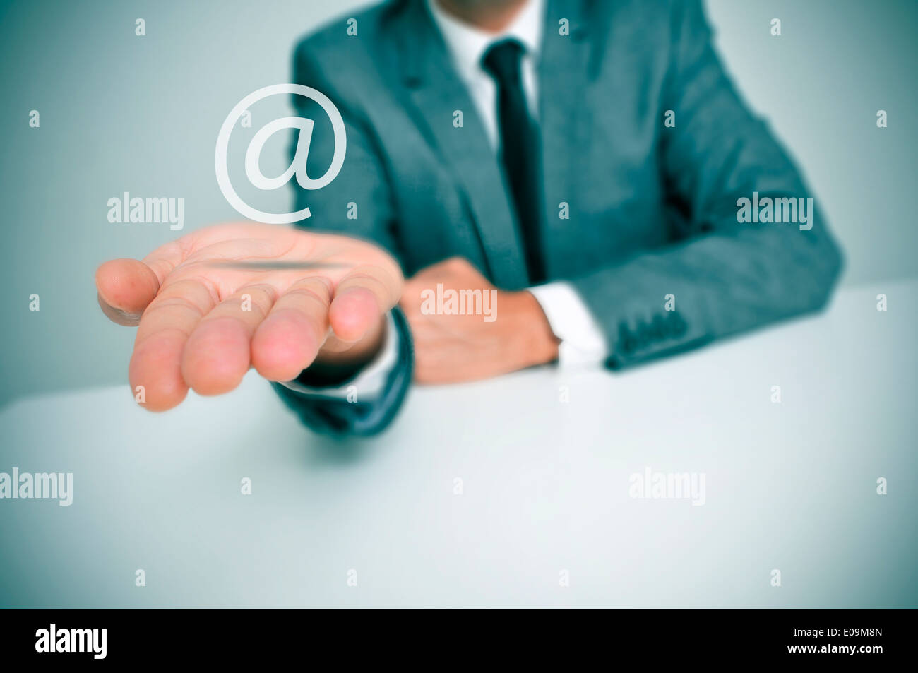 a businessman sitting in a desk with an at sign in his hand, depicting the concept of e-mail service - Stock Image