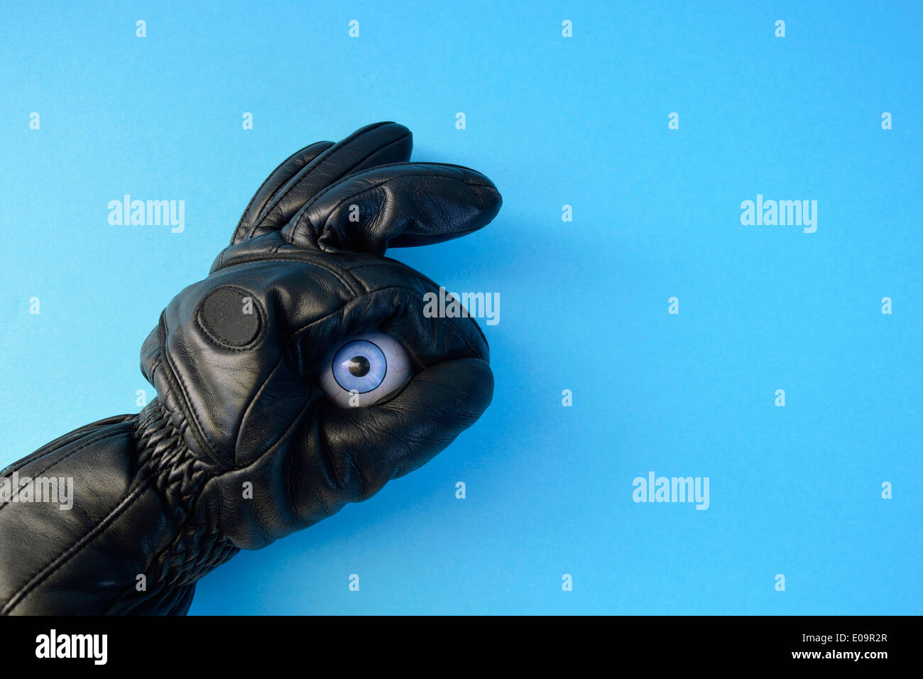 Leather glove and plastic eyeball in front of blue background - Stock Image