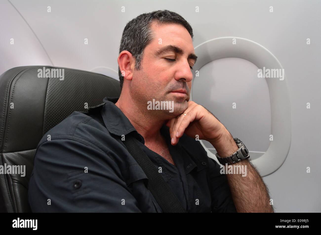 Man sleep during flight aboard a jetliner airplane. - Stock Image