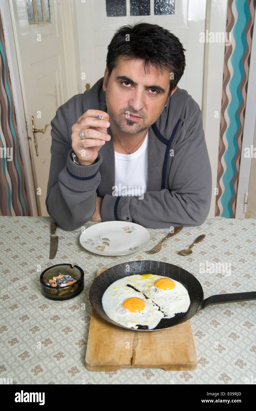 Portrait of man with bad habit sitting at breakfast table - Stock Image