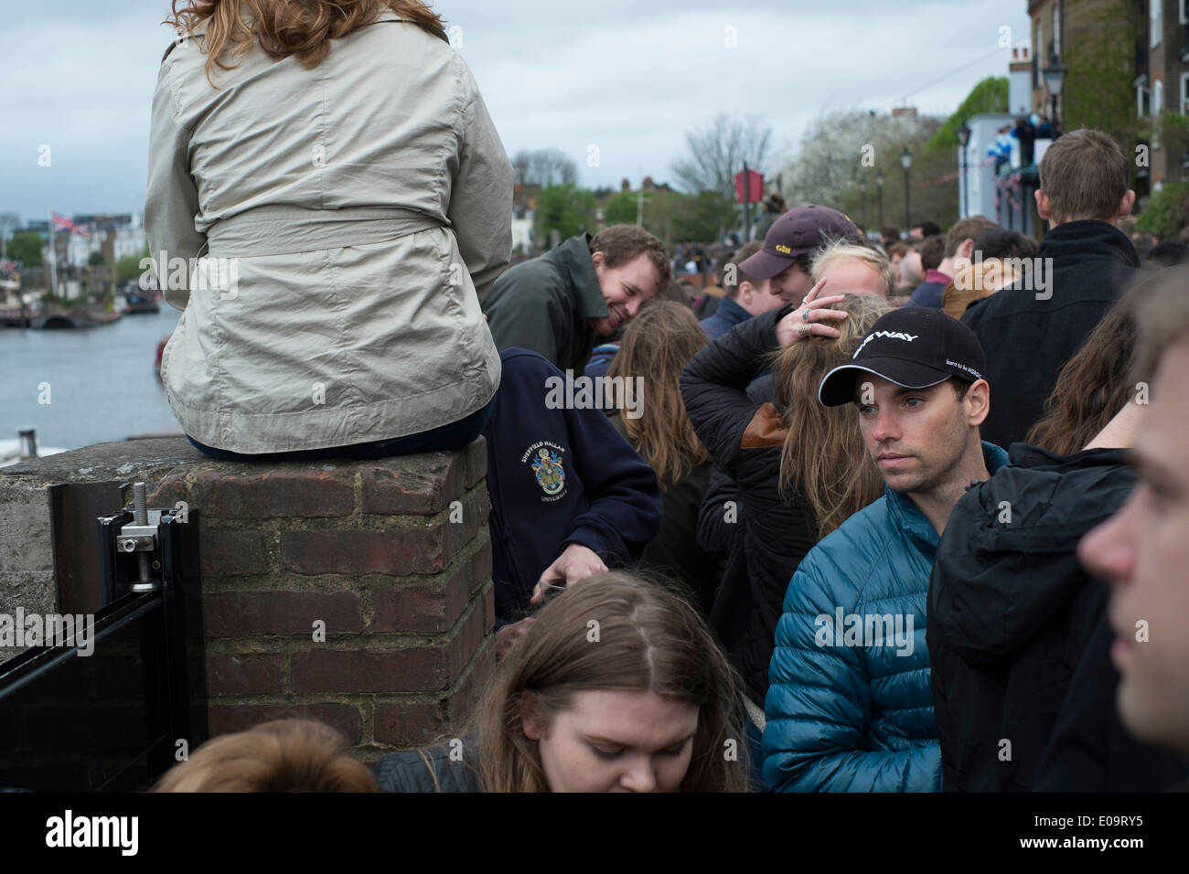 Spectators on the bank of the River Thames at Hammersmith during the annual Oxford and Cambridge Boat Race. - Stock Image