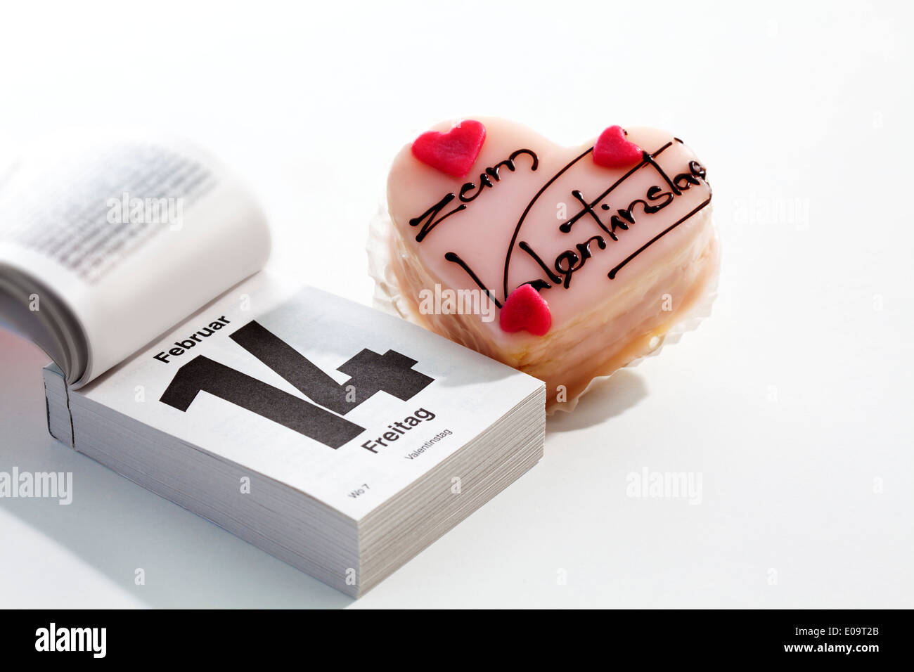 Petit four and tear-off calendar showing date of Valentine's day on white ground - Stock Image