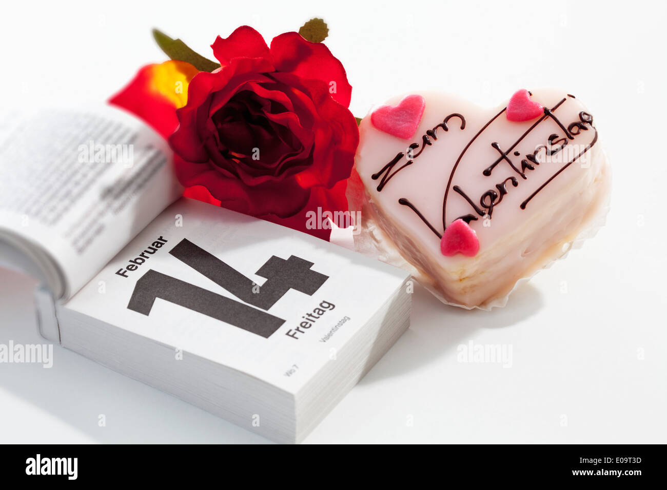 Red rose, petit four and tear-off calendar showing date of Valentine's day on white ground - Stock Image