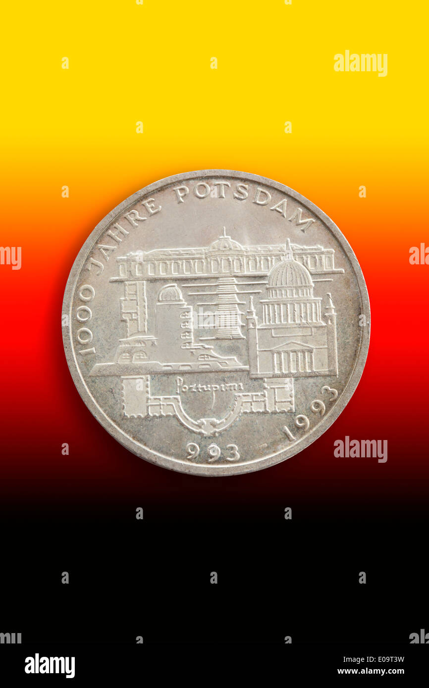 Old German commemorative coin in front of national colours - Stock Image
