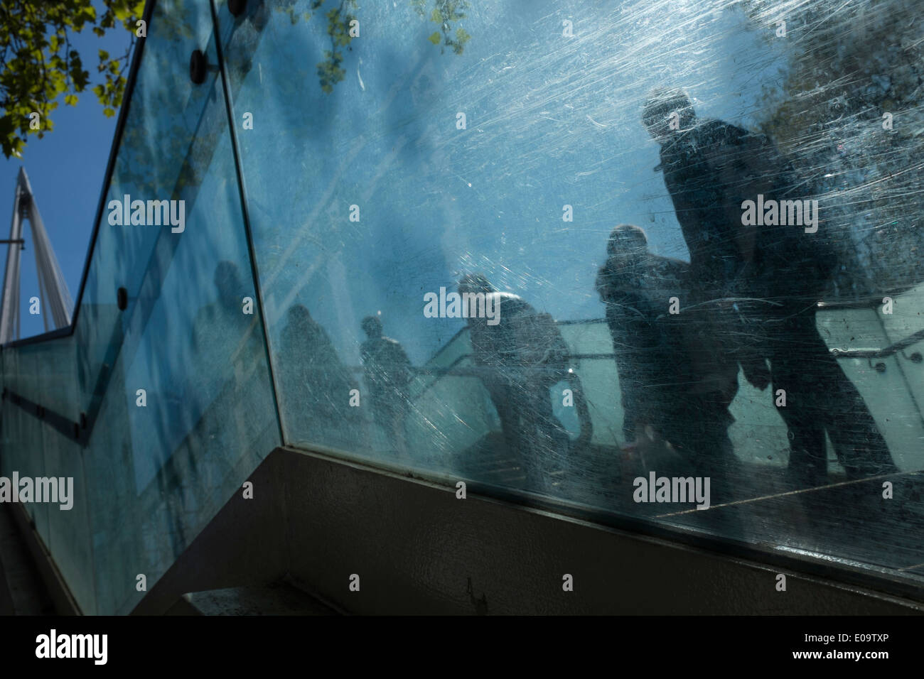 Commuters seen through the scratched glass of the stairway leading to the bridge across the River Thames. London, England - Stock Image