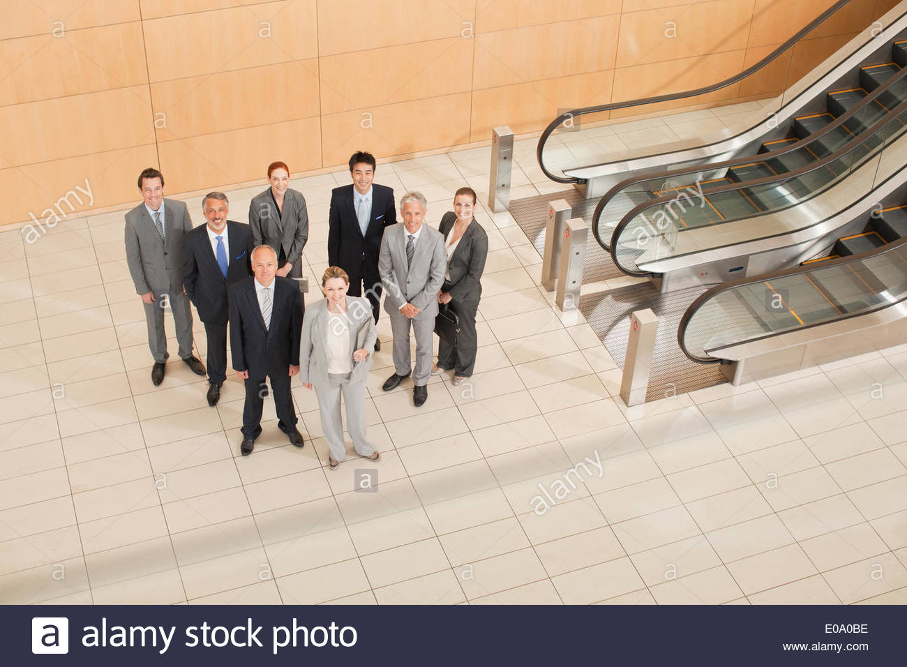 Business people at bottom of escalator - Stock Image