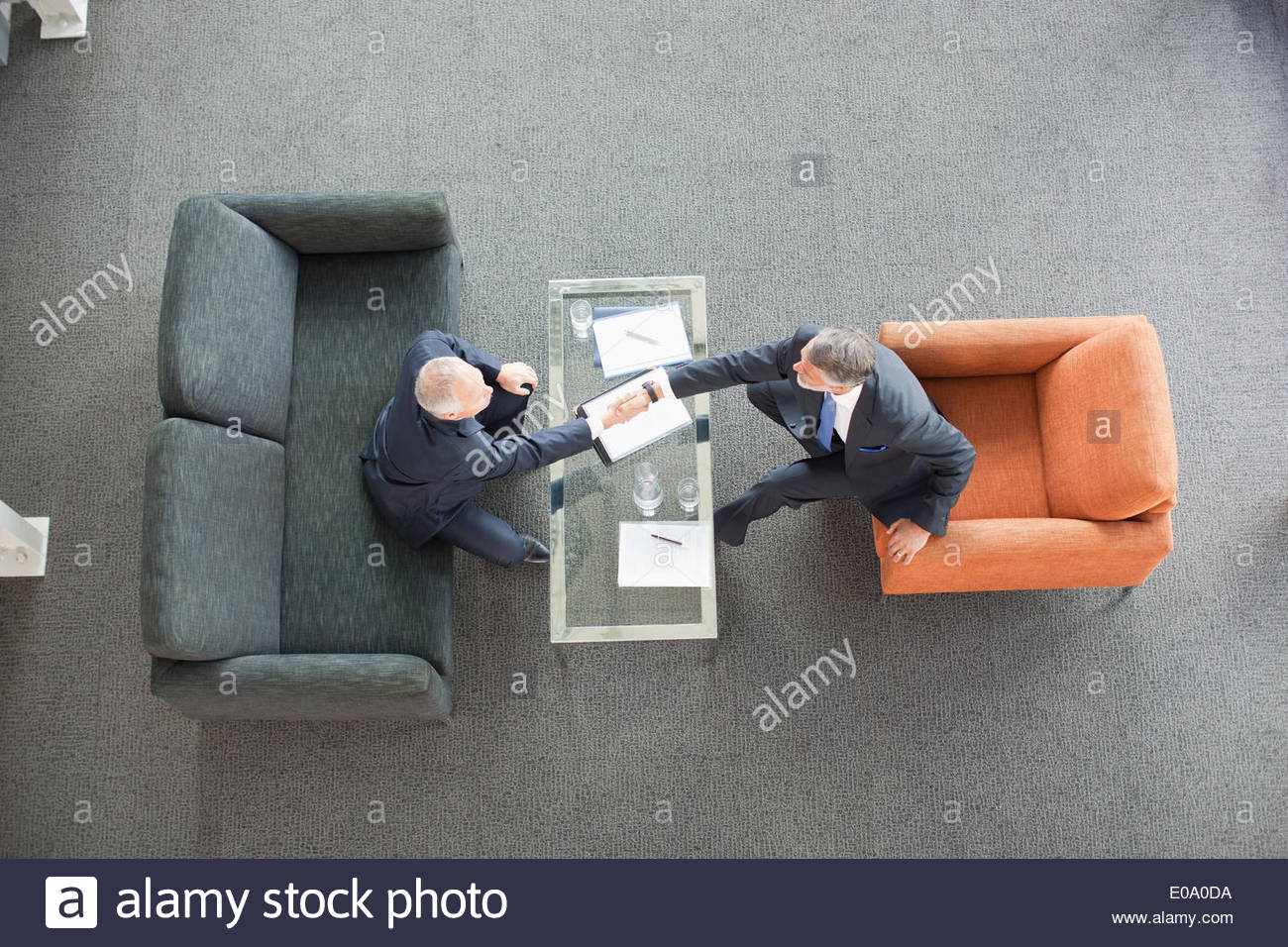Businessmen shaking hands across coffee table in lobby - Stock Image