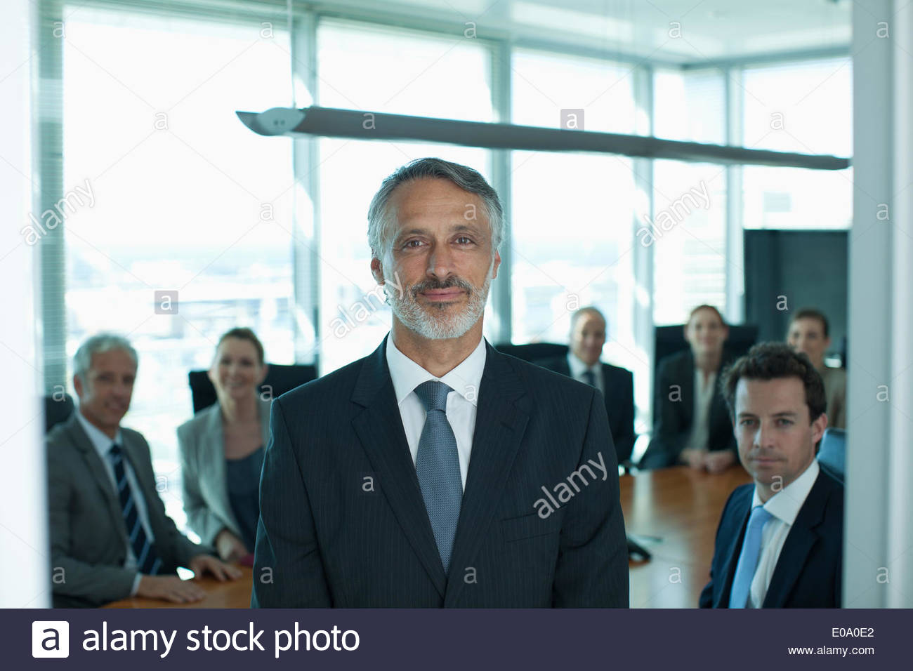 Portrait of smiling businessman and co-workers in conference room - Stock Image