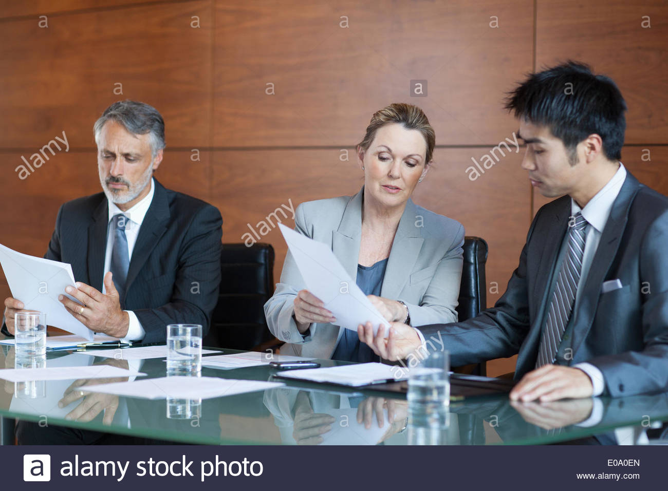 Businesswoman showing paperwork to businessman in meeting - Stock Image