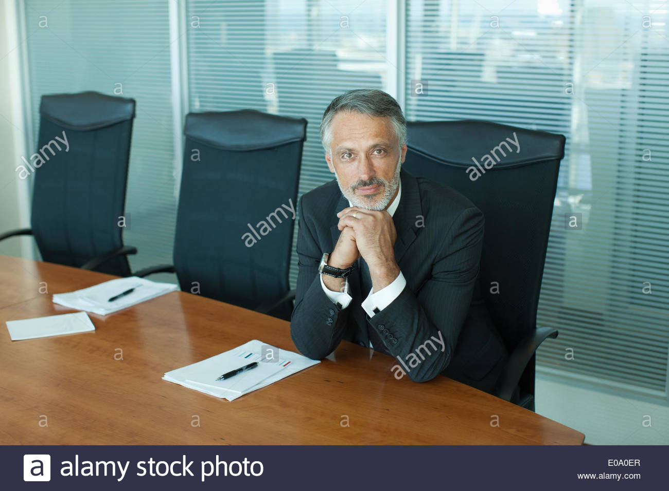 Portrait of confident businessman with hands clasped - Stock Image