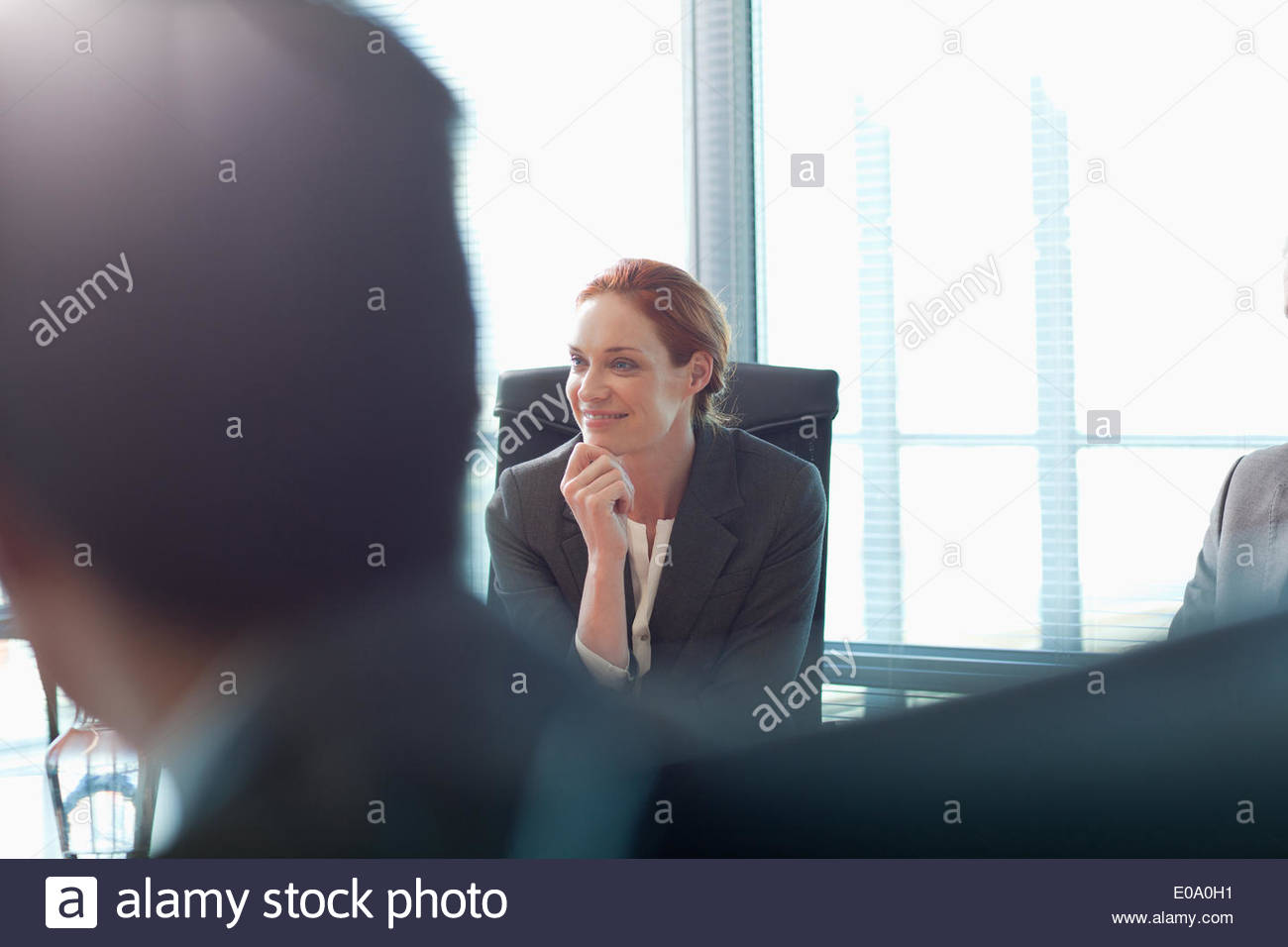 Portrait of smiling businesswoman in meeting - Stock Image