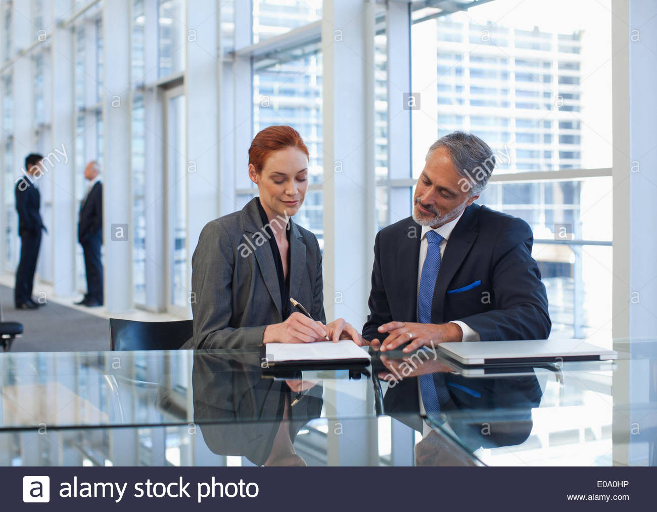 Business people talking in office lobby - Stock Image