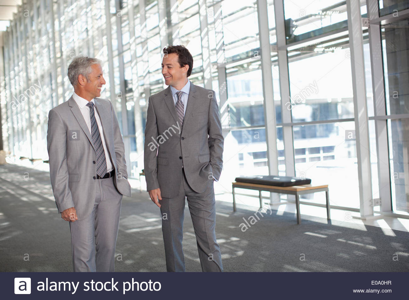 Smiling businessmen shaking hands in modern lobby - Stock Image